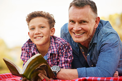 Buy stock photo Portrait of a father and son reading a book together in a park