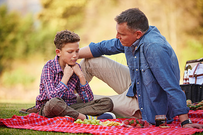 Buy stock photo Shot of a father comforting his young son while sitting in a park
