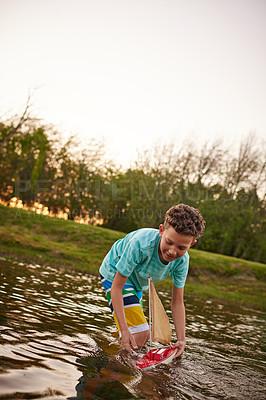 Buy stock photo Shot of a young boy standing in a lake playing with a toy boat