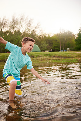 Buy stock photo Shot of a young boy splashing around in a lake