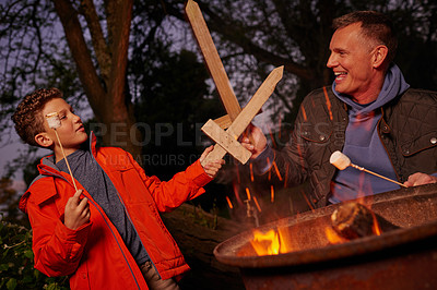 Buy stock photo Shot of a father and son playing with wood swords while toasting marshmallows over a fire