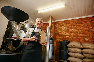 Buy stock photo Low angle portrait of a senior man holding bags of coffee beans while working in a roastery