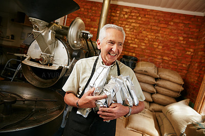 Buy stock photo Cropped shot of a senior man holding bags of coffee beans while working in a roastery