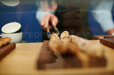 Buy stock photo Cropped shot of a deli worker choosing a bread stick from the display