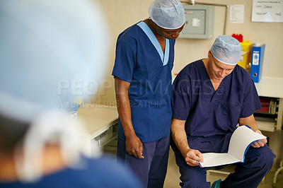 Buy stock photo Shot of surgeons going through paperwork in preparation for a surgery