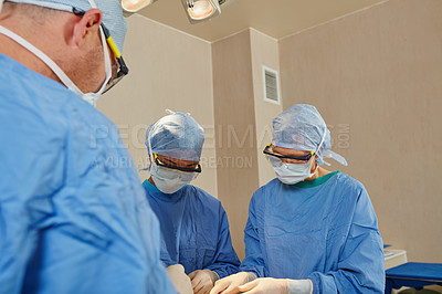 Buy stock photo Shot of a team of surgeons performing a surgical procedure in an operating room