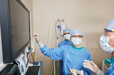 Buy stock photo Shot of a team of surgeons discussing a patient's medical scans during surgery