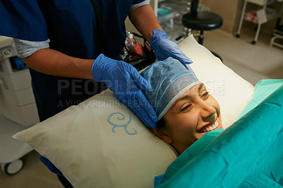 Buy stock photo Shot of a nurse putting a surgical cap on a patient in preparation for her surgery