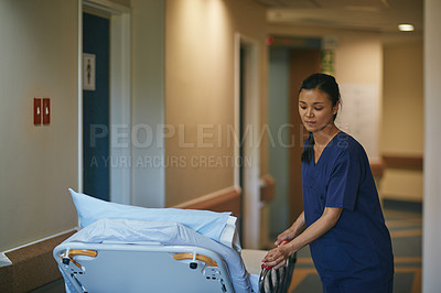 Buy stock photo Cropped shot of a female nurse pushing a hospital bed down the corridor