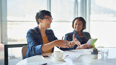 Buy stock photo Shot of two corporate businesswomen sitting in the boardroom
