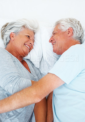 Buy stock photo Senior couple smiling and looking at each other while resting in bed