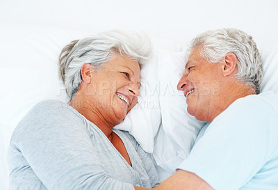 Buy stock photo Closeup of senior couple relaxing in bed and smiling lovingly at each other - copyspace