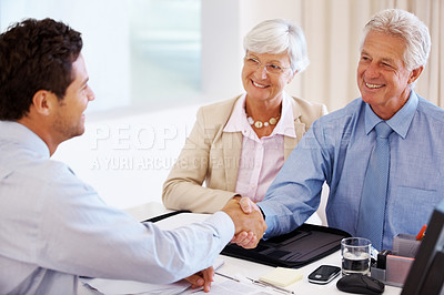 Buy stock photo Portrait of a happy old couple shaking hand with advisor in an office