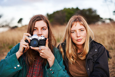 Buy stock photo Portrait of a young woman taking a picture with her friend sitting beside her while enjoying a day outdoors