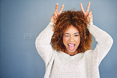 Buy stock photo Studio shot of a young woman making a bunny ear gesture against a grey background