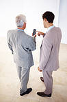 Two business men sharing information on cell phone