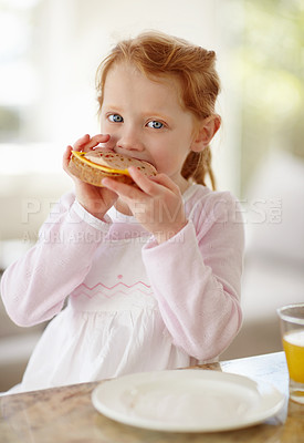 Buy stock photo Portrait of a happy adorable little girl eating sandwich for her breakfast