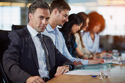 Buy stock photo Portrait of a businessman in a meeting with his colleagues in the background