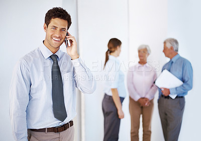 Buy stock photo Smart young businessman speaking on mobile phone with colleagues in background