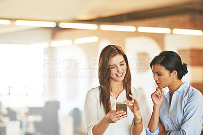 Buy stock photo Shot of two coworkers talking together over a cellphone while standing in an office