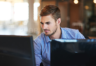 Buy stock photo Shot of a young businessman using a computer in an office