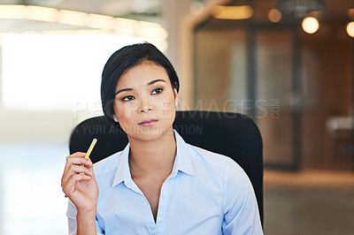 Buy stock photo Shot of a thoughtful young businesswoman working in the office