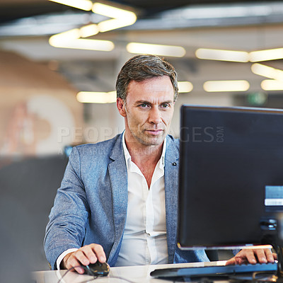 Buy stock photo Shot of a mature businessman using a computer in an office