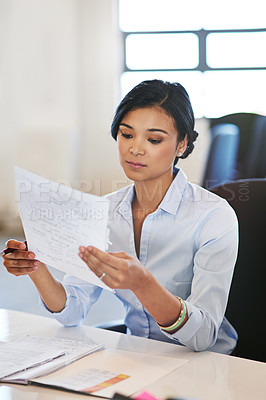 Buy stock photo Shot of a young businesswoman reading a document in an office