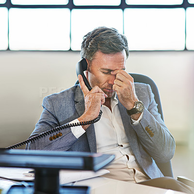 Buy stock photo Shot of a mature businessman looking stressed while talking on the phone