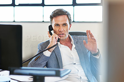 Buy stock photo Shot of a mature businessman making a serious call on the phone at work