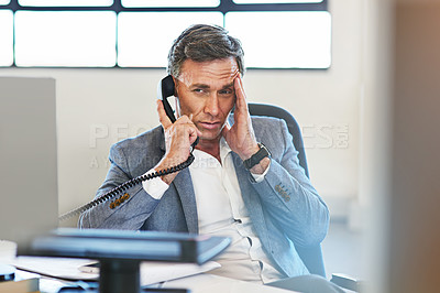Buy stock photo hot of a mature businessman looking stressed while talking on the phone