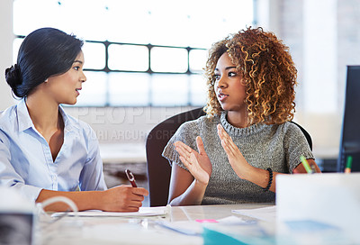 Buy stock photo Shot of two colleagues having a discussion in an office