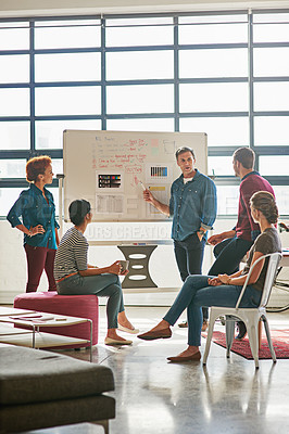 Buy stock photo Shot of designers brainstorming on a whiteboard in an office