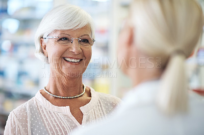 Buy stock photo Shot of a pharmacist helping an elderly customer