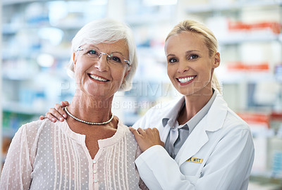 Buy stock photo Portrait of of a happy young pharmacist standing next to an elderly customer