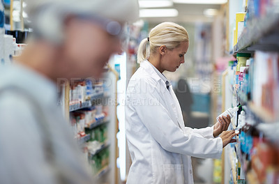 Buy stock photo Shot of a young pharmacist checking stock in an aisle