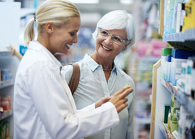 Buy stock photo Shot of a young pharmacist helping an elderly customer