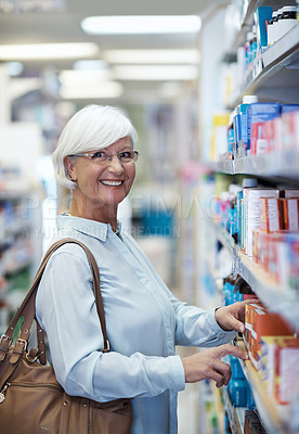 Buy stock photo Shot of an elderly woman looking at products in a pharmacy