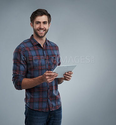 Buy stock photo Studio portrait of a young man using a digital tablet against a grey background