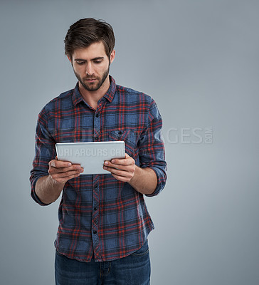 Buy stock photo Studio shot of a young man using a digital tablet against a grey background