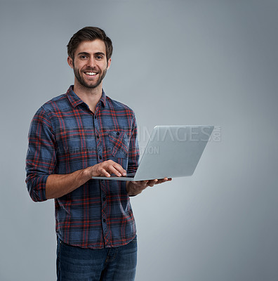 Buy stock photo Studio shot of a young man using a laptop against a grey background