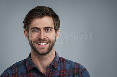 Buy stock photo Studio portrait of a smiling young man against a grey background