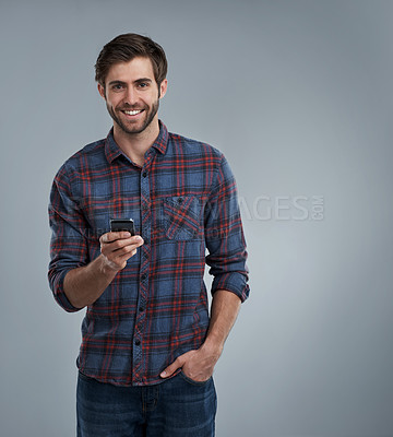 Buy stock photo Studio portrait of a smiling young man using a cellphone against a grey background