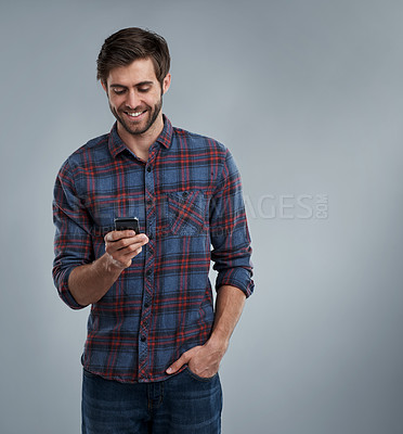 Buy stock photo Studio shot of a smiling young man using a cellphone against a grey background