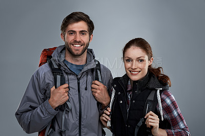 Buy stock photo Studio portrait of two young backpackers against a gray background