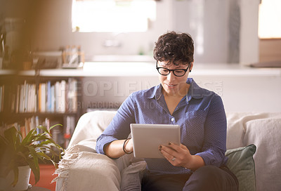 Buy stock photo Cropped shot of a mature woman using her tablet while sitting on the sofa at home