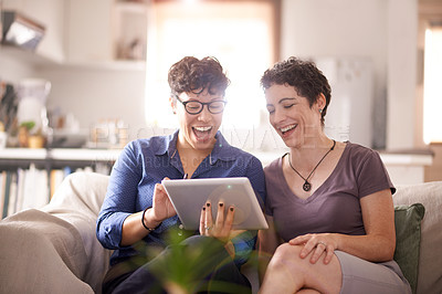 Buy stock photo Shot of a happy couple using a digital tablet at home