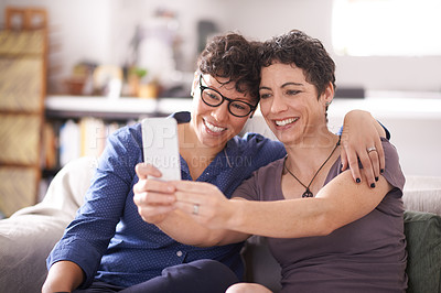 Buy stock photo Shot of a happy couple taking a selfie together at home