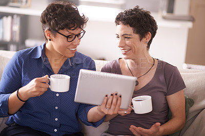 Buy stock photo Shot of a happy couple using a digital tablet together at home