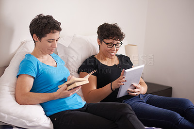 Buy stock photo Shot of a woman reading a book while her wife uses a digital tablet at home